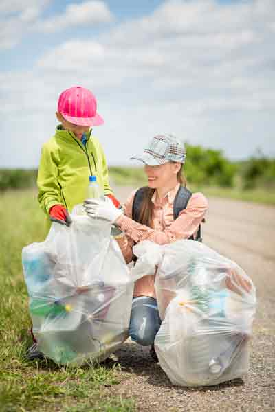 woman and child picking up trash with bag